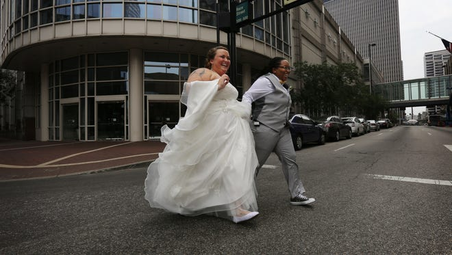 After getting their pictures taken, Chelsey Wright, nee Castrucci, and Christian Wright, both of Colerain Twp., run back to the Hall of Mirrors Downtown before their wedding ceremony.