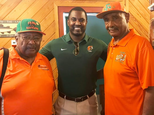Football head coach Willie Simmons, center, shares