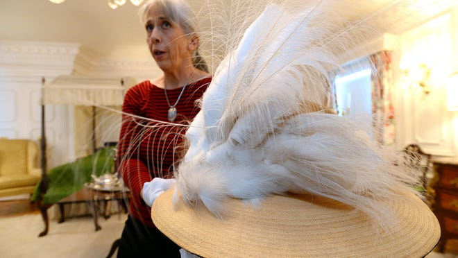 Director Elizabeth Guheen shows a hat pulled out of storage for Upstairs Downstairs Day at the Charles M. Bair Family Museum in Martinsdale, which will allow visitors to tour the upstairs rooms of the Bair ranch house. She's in a white elegant downstairs room. The simple rooms, where the Bair sisters actually slept, were upstairs.