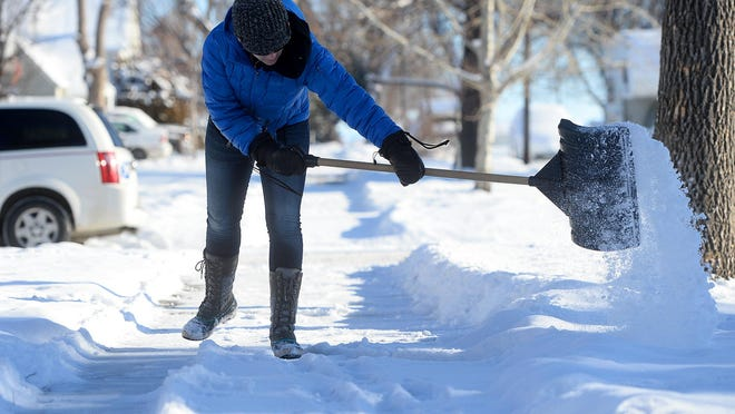 Tiffany Grundel shovels the sidewalk for her neighbor on Wednesday morning on 3rd Avenue North in Great Falls. Grundel says she tries to stay on top of keeping the sidewalks on her block clear because there is so much foot traffic. There's about a 50-50 chance snow will stick around for Christmas, according to the National Weather Service in Great Falls.