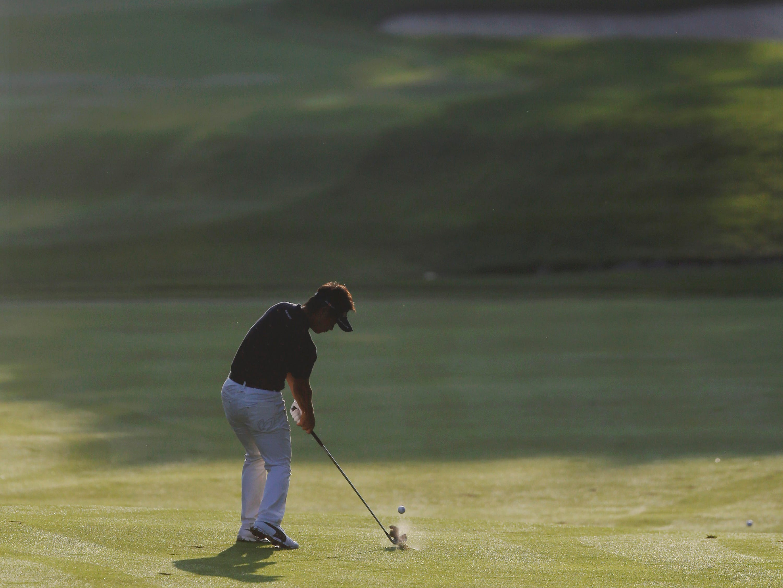 Hiroyuki Fujita hits from the fairway on the 10th hole.
