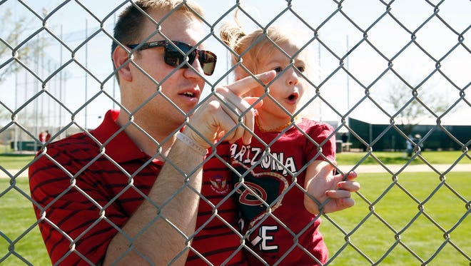 Andrew Curtis and his daughter Aria, age 3 from Gilbert, Ariz., watch the Arizona Diamondbacks take batting practice at spring training camp in Scottsdale, Ariz., on Friday, February 26, 2016.
