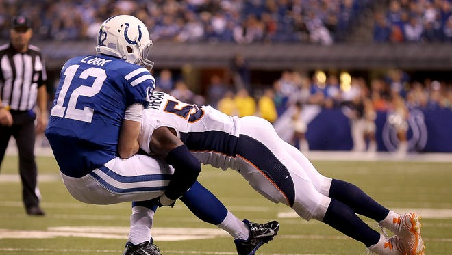 Indianapolis Colts quarterback Andrew Luck (12) is hit by Denver Broncos inside linebacker Danny Trevathan (59) early in the during the fourth quarter in their game Sunday, Nov. 8, 2015, at Lucas Oil Stadium.