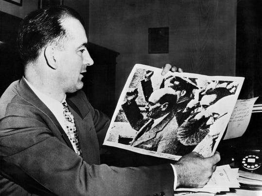 US Senator Joseph McCarthy holds a picture showing