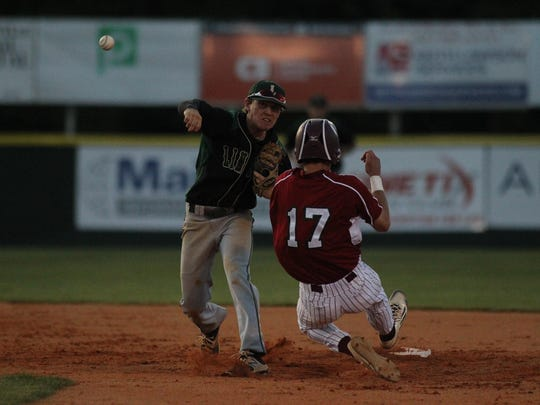 Lincoln second baseman Connor Burk turns a double play as Chiles' Tommy Kinney slides past during Wednesday's District 2-8A championship.