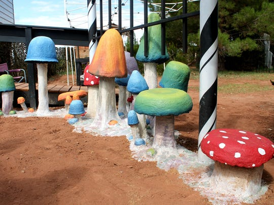 A pathway of colorful concrete mushrooms lead the way to Horror Hall's new spinning tunnel attraction.