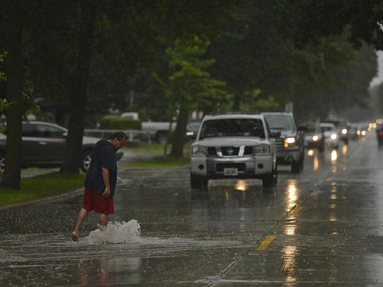 Randal Cloud uses his foot to hold down a manhole cover along 12th Avenue. in Green Bay on Monday. Downtown streets were flooded due to the heavy rainfall on Monday afternoon.
