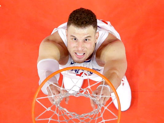 Los Angeles Clippers forward Blake Griffin hangs on the net after throwing the ball out of bounds while trying to pass it to guard Lou Williams with seconds left in an NBA basketball game against the Minnesota Timberwolves, Monday, Jan. 22, 2018, in Los Angeles. The Timberwolves won 126-118. (AP Photo/Mark J. Terrill)