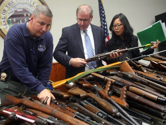 From left: Capt. James Russo of the Union County Prosecutor's Office, acting Union County Sheriff Joe Cryan and acting Union County Prosecutor Grace Park look over nearly 500 firearms purchased in a Union County gun buyback program Monday at the Ralph Froehlich Union County Public Safety Building in Westfield.