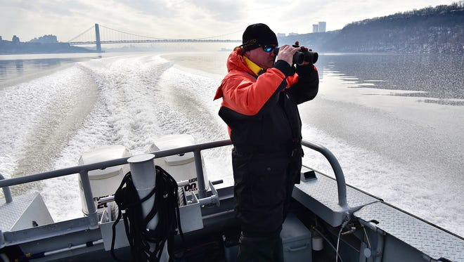 Richard Paull, chief of the DEP water enforcement's northern bureau, scans the shoreline north of the George Washington Bridge during a routine patrol Feb. 15.