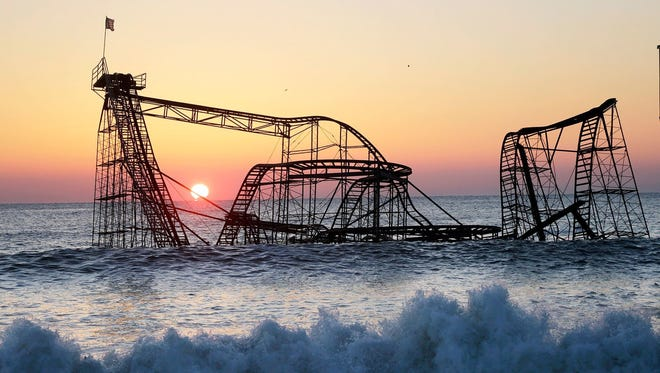 A roller coaster sits in the surf off Seaside Heights, Ocean County, after Superstorm Sandy. A Camden woman has been ordered to pay more than $50,000 after falsely claiming damages from the 2012 storm.