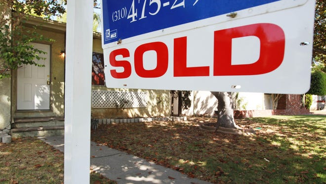 """In this June 23, 2009, photo, a """"sold"""" sign is seen on a home for sale in Los Angeles."""
