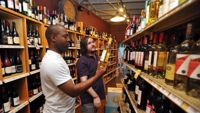 Employee Sam Wigglersworth (right) helps Steven Johnson with his selection Friday at Briarwood Wine and Spirits on Old Canton Road in Jackson. The store is always open on July 4, says owner Nathan McHardy.