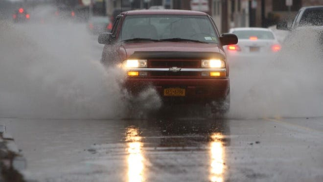A truck drives through the rain on East Avenue Friday morning in Rochester.