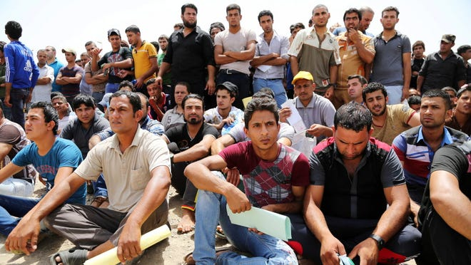 Iraqis gather in Baghdad to volunteer for military service Thursday.