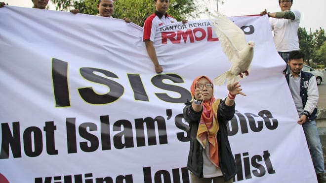 Releasing a dove at Friday's rally in Jakarta, Indonesia. The banner reads: ISIS is not Islam's voice. Stop Killing Journalist.