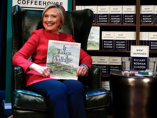 "Hillary Clinton, holds her book ""It Takes A Village"""