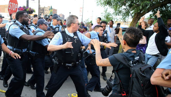 Members of the Chicago police department scuffle with an angry crowd at the scene of a police-involved shooting in Chicago on July 14, 2018.