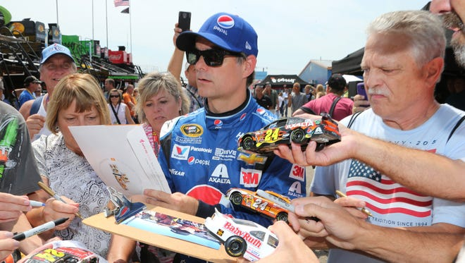 Jeff Gordon signs autographs before a practice session Friday, Aug. 14, 2015, for Sunday's NASCAR Sprint Cup series auto race at Michigan International Speedway in Brooklyn, Mich.
