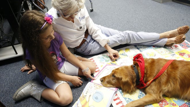 """Second grader Mariangel Castillo, 7, reads the book """"Z is for Moose"""" with Leon County Schools volunteer mentor Sarah Sherraden and her golden retriever Snuggles at Gilchrist Elementary School. The program, called Reading Education Assistance Dogs, or R.E.A.D, is designed to help kids feel more confident in reading aloud."""