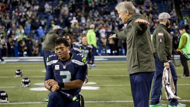 Seattle Seahawks quarterback Russell Wilson, left, talks with head coach Pete Carroll before an NFL football game, Sunday against the Arizona Cardinals, Nov. 15, 2015, in Seattle.