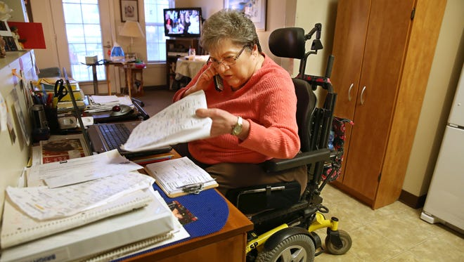 Carol Ortis works at her desk organizing needed rides in her Webster home Thursday, Jan. 14, 2016.  Orits may have Guillain-Barre syndrome, but she doesn't let it slow her down or stop her from giving back to her community.