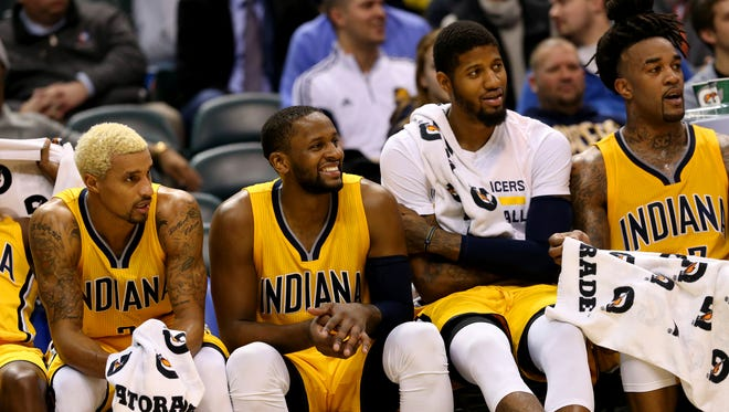 Indiana Pacers teammates George Hill (3), C.J. Miles (0), Paul George (13) and Jordan Hill (27) sit on the bench as the time ticks off the clock in the win against the Toronto Raptors at Bankers Life Fieldhouse on Dec. 14, 2015.