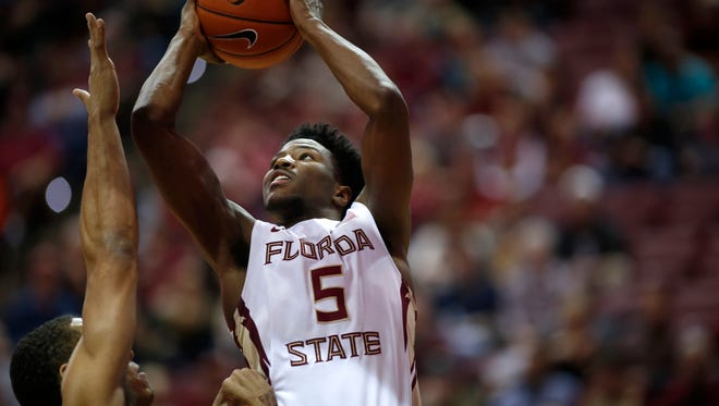 FSU's Malik Beasley takes a shot over Virginia's Malcolm Brogdon during their game at the Tucker Civic Center on Sunday.