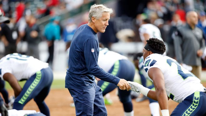 Seattle Seahawks head coach Pete Carroll shakes hands with players before a preseason NFL football game against the Oakland Raiders Thursday, Sept. 1, 2016, in Oakland, Calif.