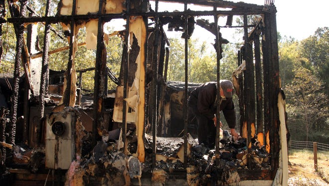Jerry Hart sifts through debris at his twin sister's home, hours after she died in a fire.