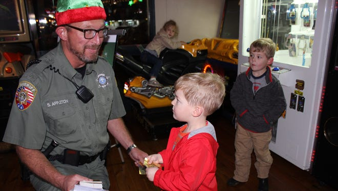 School Resource Officer Scot Appleton accepts a donation from Miles Holland at the 2015 Shop with the Sheriff's Office fund-raiser at Toot's. With Miles are his sister, Ellie, and brother, Hudson.