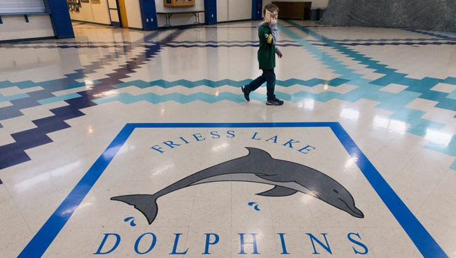 A student walks to his classroom after visiting the office at Friess Lake School in Richfield.