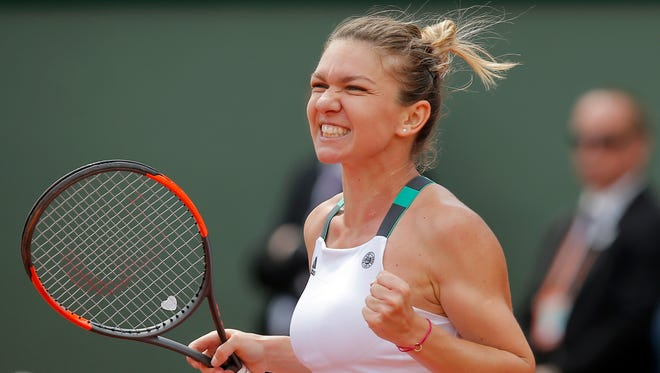 Romania's Simona Halep celebrates winning her fourth round match against Spain's Carla Suarez Navarro in two sets, 6-1, 6-1, at the French Open at the Roland Garros stadium, in Paris on June 5.