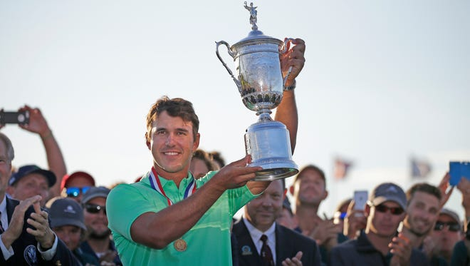 Brooks Koepka holds up the U.S. Open Championship trophy at Erin Hills after his four-shot victory Sunday.