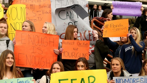 Central Kitsap High School students hold signs while