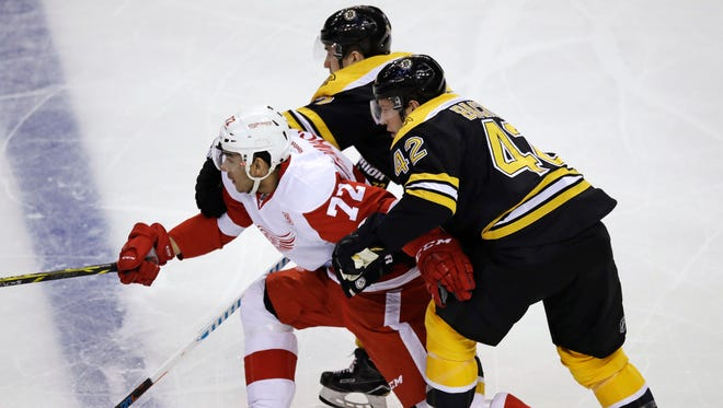 Red Wings center Andreas Athanasiou (72) is held back as he threads between two Bruins defenders.