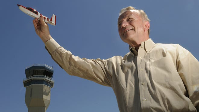 Tom Poberezny, former president and CEO of the Experimental Aircraft Association, holds up a model airplane outside the new control tower at Wittman Regional Airport in this 2008 file photo.