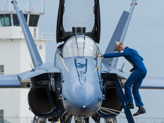 Lt. Brandon Hempler, of the Blue Angels, dismounts from his Boeing F/A-18 Hornet during a media event at Wallops Flight Facility on Tuesday, Nov. 29, 2016.
