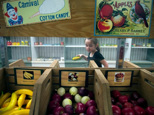 Emma Gumpert shops for plastic fruit and vegetables in a grocery exhibit at the Paws Discovery Farm last year. The farm is hosting a Barnyard Bash this weekend to celebrate its one-year anniversary since it re-opened under a new name, and to celebrate the grand re-opening of Discovery Barn.