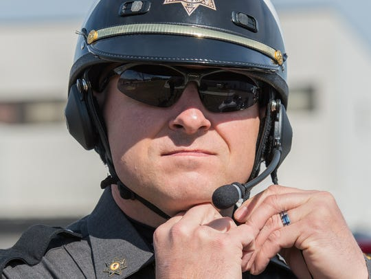 DFC Jeff Chase fastens his motorcycle helmet just before