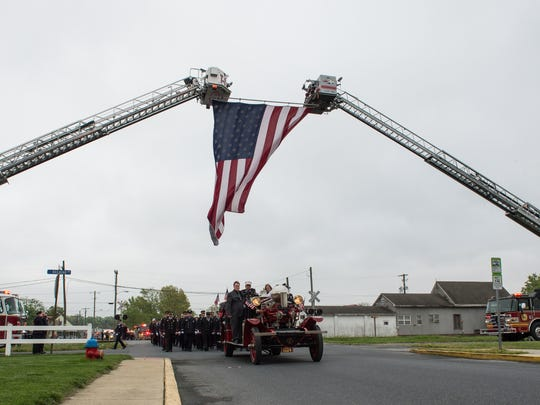 A funeral procession for Laurel firefighter Alan Schweitzer passes underneath an American flag on 10th Street.