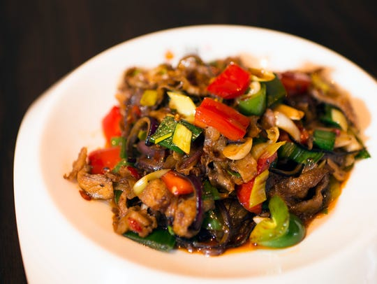 Twice Cooked Pork ($13.99) is thinly sliced pork belly stir fried with chilies, bell peppers, onions, leeks,  and then a sauce, a little bit of black bean sauce. It's deeply savory and juicy, and the vegetables are simultaneously silky and crunchy.