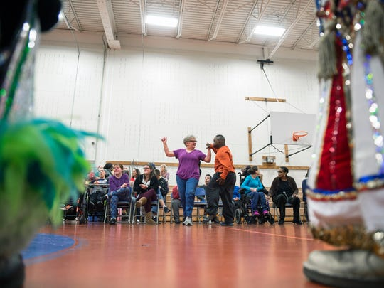 Helen Scherer, left, dances with her student Taj Brown, 20, as mummers perform for students at Burlington County Special Services School Friday, Dec. 1, 2017 in Westampton, New Jersey.