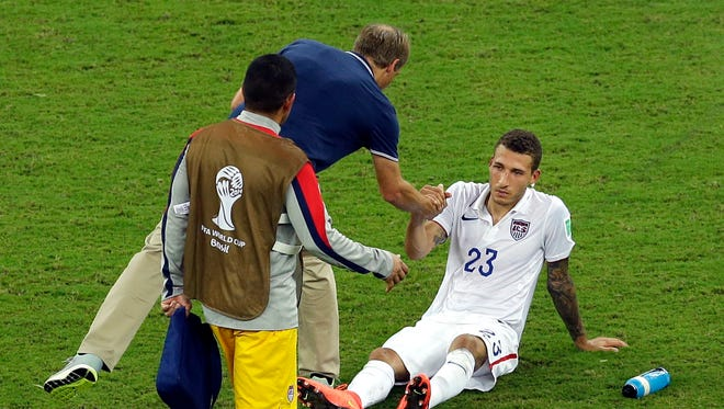 United States' Fabian Johnson, right, shakes hand with head coach Juergen Klinsmann after a 2-2 draw in the group G World Cup soccer match between the USA and Portugal at the Arena da Amazonia in Manaus, Brazil, Sunday, June 22, 2014.
