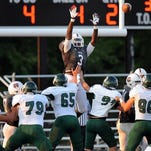 Lawrence Central's Quintaz Wrights leaps in the air while trying to block a field goal attempt by Louisville Trinity in the first half of the game held at Lawrence Central High School on Friday, September 6, 2013.