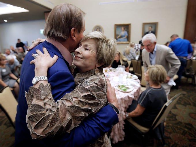 Marlene Stewart hugs El Paso businessman and family