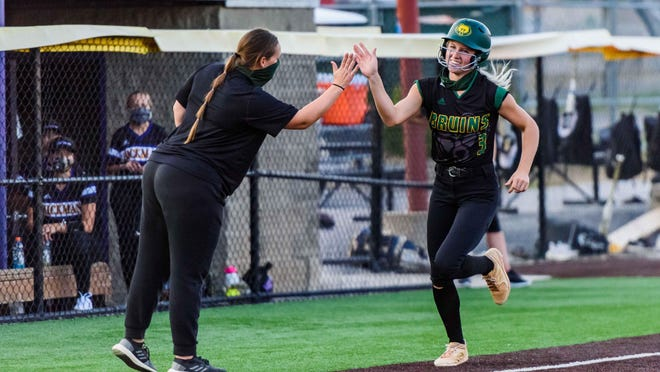 Rock Bridge's Maddie Snider (3) high-fives head coach Lisa Alvis as she rounds third base after hitting her first of two home runs during a game against Hickman on Thursday night at Hickman High School.
