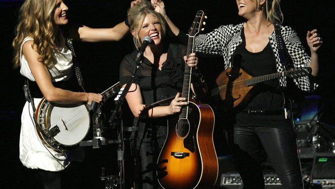 """In this Oct. 18, 2007 file photo, Emily Robison, left, and Martie Maguire, right, adjust Natalie Maines' hair as the Dixie Chicks perform at the new Nokia Theatre in Los Angeles. The Grammy-winning country group, who recently changed their name to The Chicks, have a new album """"Gaslighter,"""" which was released Friday."""