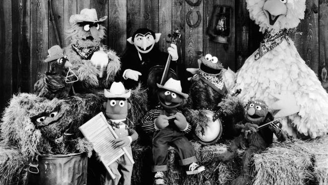 A publicity still of the Sesame Street Muppets was taken to promote their record album, 'Sesame Country,' in July 1981. Included are Oscar the Crouch (in garbage can), Bert (holding washboard), Ernie (harmonica), the Count (bass), Cookie Monster (banjo), Grover (violin), and Big Bird (far right).