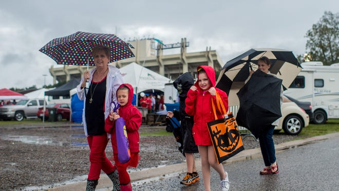 Darlene Abshire Rhyan Dubois, 5, Cade Buccholz, 9, Caitlin Buchholz, 7, Stephanie Buchholz, walk through the tailgating area while trick-or-treating at Cajun Field in Lafayette, La., Saturday, Oct. 31, 2015.